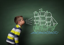 Child blowing a chalk sailboat. Child blowing a chalk drawing of a sailboat on a blackboard concept for wishing, dreams, hope and aspirations Stock Image