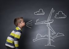 Child blowing a chalk wind turbine. Child blowing a chalk drawing of a wind turbine on a blackboard concept for alternative renewable energy and education of the royalty free stock image