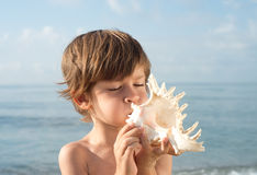 Child blowing conch. Looking up at sea Royalty Free Stock Photography