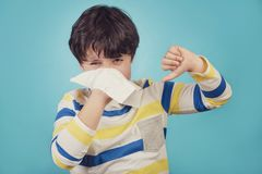 Child blowing the nose has a cold. On blue background Royalty Free Stock Image