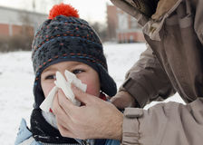 Child blowing nose. Parent helping a child to blow nose in winter outdoor Royalty Free Stock Photography