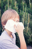 Child blowing nose with tissue paper at the park Royalty Free Stock Photography