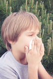 Child blowing nose with tissue paper at the park Stock Photos