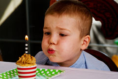 Child blowing out candle Royalty Free Stock Images