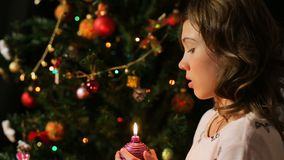 Child blowing out decorated Christmas candle and making a wish, magic moments. Stock footage stock footage