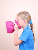Child blowing pink paper bag. Profile portrait of a cute little Caucasian school girl blowing up a pink paper bag Stock Photo