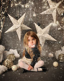 Child Blowing Snow on Winter Background. A little child is sitting on a winter wonderland backdrop with trees and white stars. She is blowing snow in her hand stock image