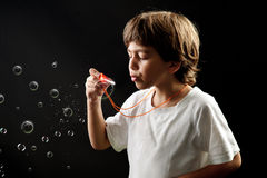 Child blowing soap bubbles Stock Photo