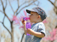 Child Blowing Soap Bubbles. Boy blowing soap bubbles on a spring day. He's wearing blue baseball cap and blue t-shirt Stock Photo