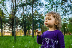 Child blowing soap bubbles. Stock Photo