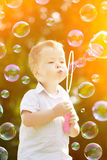 Child blowing a soap bubbles. Boy playing. Kid blowing bubbles o Stock Images
