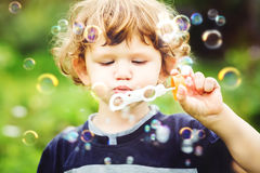Child blowing soap bubbles, closeup portrait. Stock Images