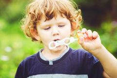 Child blowing soap bubbles, closeup portrait Stock Photo