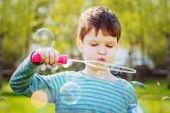 Child blowing soap bubbles, closeup portrait beautiful boy. Stock Image