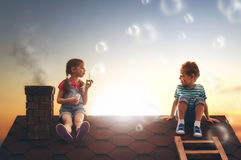 Child blowing soap bubbles. Happy childhood! boy and girl playing on the roof. child blowing soap bubbles Royalty Free Stock Photography