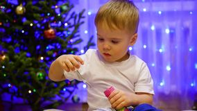 Child blowing soap bubbles at home. In the background, bokeh lights and garlands. stock footage