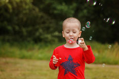 Child blowing a soap bubbles. Kid blowing bubbles on nature Royalty Free Stock Photos