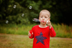 Child blowing a soap bubbles. Kid blowing bubbles on nature. Stock Images