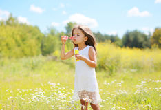 Child blowing soap bubbles on meadow in sunny summer Stock Photos