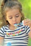 Child blowing soap bubbles Stock Photos