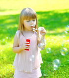 Child blowing soap bubbles outdoors Stock Photos