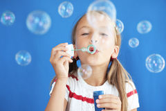 Child blowing soap bubbles. Portrait of funny lovely little girl blowing soap bubbles Stock Photography