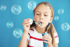 Child blowing soap bubbles Stock Image