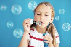 Child blowing soap bubbles stock image
