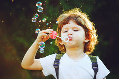 Child blowing soap bubbles in summer park. Stock Photo