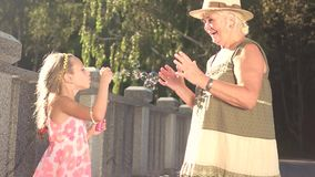 Child blowing soap bubbles to her grandmother. stock video footage