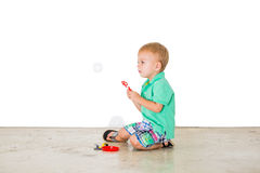 Child blowing soap bubbles in white background Royalty Free Stock Photography