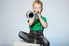 Child Blowing Trumpet. Isolated Young Boy Blowing Trumpet Royalty Free Stock Photo