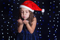 Child is blowing white snowflakes in a studio Royalty Free Stock Images