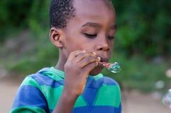 Child blows bubbles. Little boy blows air bubbles Stock Photo