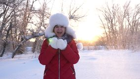 Child blows snowflakes from hands in winter park, in christmas vacation. Happy girl blowing snowflakes at sunset and. Child blows snowflakes from hands in winter stock video footage