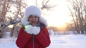 Child blows snowflakes from hands in winter park, in christmas vacation. Happy girl blowing snowflakes at sunset and. Child blows snowflakes from hands in winter stock footage