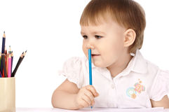 Child with blue crayon think about drawings Stock Photos