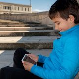 Smiling young boy sitting on the floor using a digital tablet stock images