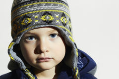Child with blue eyes.fashion kids.fashionable little boy in winter cap. Close-up Portrait of child with blue eyes.fashion kids.fashionable little boy in winter Stock Photo