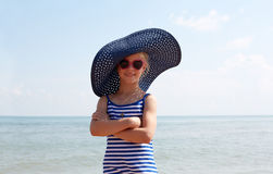 Child in blue hat on against sea and sky background. Royalty Free Stock Image