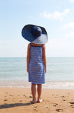 Child in blue hat on against sea and sky background. Stock Image