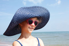 Child in blue hat on against sea and sky background. Royalty Free Stock Photo