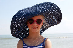 Child in blue hat on against sea and sky background. Stock Photos