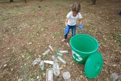 Child in blue latex gloves, throwing plastic bag into recycling bin. Land and rubbish on the background, outside photo, Stock Images