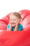 Child in blue shirt on red pouf chair Stock Photos
