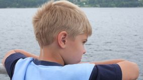Child on boat looks into the distance. Closeup stock footage