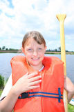 Child boating. A happy and smiling girl in an orange life vest, holding a canoe paddle in front of a pond stock image