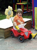 Child on a bobby car. Child on a red bobby car, all trademarks and copyrights are are removed royalty free stock images