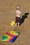 Child with Boogie Board. A young, blond boy stands on a golden sand beach with his yellow bucket and colourful boogie board Royalty Free Stock Images