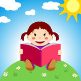 Child with book. Happy child reads a book on the grass under the sun Royalty Free Stock Images